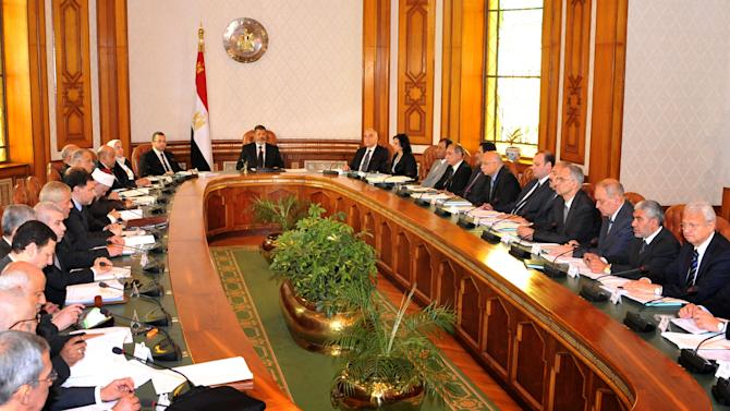 In this image released by the Egyptian Presidency, Mohammed Morsi, center, meets with his cabinet in Cairo, Egypt, Tuesday, May 7, 2013. Nine new Egyptian ministers joined President Mohammed Morsi's Cabinet on Tuesday, including two members of his Muslim Brotherhood, in a reshuffle that officials said was aimed at addressing the country's financial woes and securing a much-needed international loan. (AP Photo/Egyptian Presidency)