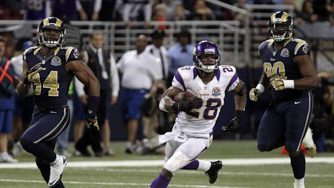 CORRECTS TO A 52-YARD GAIN, NOT TOUCHDOWN - Minnesota Vikings running back Adrian Peterson, center, runs past St. Louis Rams defenders Robert Quinn, left, and Michael Brockers on his way to a 52-yard gain during the fourth quarter of an NFL football game Sunday, Dec. 16, 2012, in St. Louis. The Vikings won 36-22. (AP Photo/Seth Perlman)