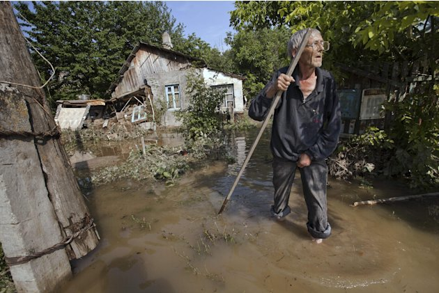 A local resident stands at a flooded house in Krimsk, about 1,200 kilometers (750 miles) south of Moscow, Russia, Sunday, July 8, 2012. The death toll from severe flooding in the Black Sea region of s