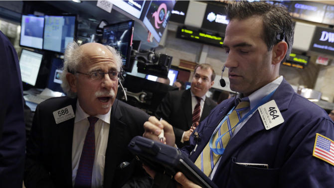 Traders Peter Tuchman, left, and Gregory Rowe work on the floor of the New York Stock Exchange Wednesday, Oct. 9, 2013. World stock markets were dragged down Friday Oct. 25,2013 by doubts about the durability of recoveries in Asia's two biggest economies. (AP Photo/Richard Drew)