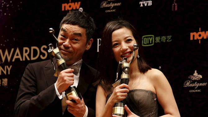 Hong Kong actor Sean Lau and Chinese actress Zhao Wei pose with their trophies after winning the Best Actor and Best Actress awards at Hong Kong Film Awards