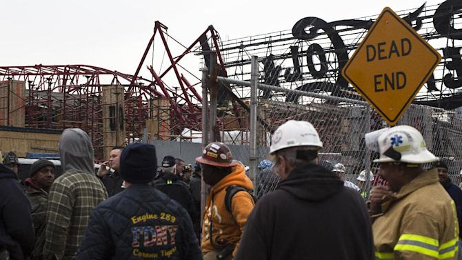 A mangled crane, upper left, lies at the construction site in the Queens borough of New York where it collapsed, Wednesday, Jan. 9, 2013. The Fire Department of New York says the 200-foot crane collapsed onto a building under construction, injuring seven people, three of them seriously. (AP Photo/John Minchillo)