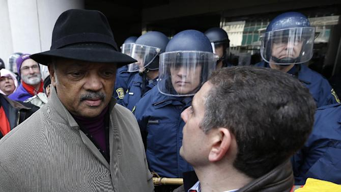 Rev. Jesse Jackson, left, and Lansing Mayor Virg Bernero, right, try to enter past Michigan State Police at the George W. Romney State Building, where Gov. Snyder has an office in Lansing, Mich., Tuesday, Dec. 11, 2012. The crowd is protesting right-to-work legislation passed last week. Michigan could become the 24th state with a right-to-work law next week. Rules required a five-day wait before the House and Senate vote on each other's bills; lawmakers are scheduled to reconvene Tuesday and Gov. Snyder has pledged to sign the bills into law. (AP Photo/Paul Sancya)