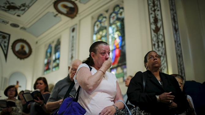 A woman cries while people attend the last mass at Church of Our Lady of Peace in New York