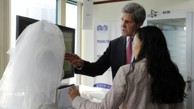 U.S. Secretary of State John Kerry looks at a wedding dress created by Lihn Thai, front, founder and CEO of The One Couture, during a business event in Ho Chi Minh City, Vietnam Saturday, Dec. 14, 2013. Forty-four years after first setting foot in the country as a young naval officer, Kerry returned once more to Vietnam on Saturday, this time as America's top diplomat offering security assurances and seeking to promote democratic and economic reform. (AP Photo/Brian Snyder, Pool)