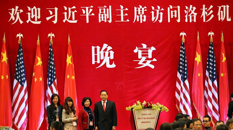 """In this Feb. 16, 2012 photo released by Anna Wu, Chinese-American businessman Vincent Wu, fourth from left, stands on stage with his wife Yip Lai Fong, third from left, daughter Anna Wu, second from left, and another relative, Even Wu, before a banquet to welcome China's then-Vice President Xi Jinping on his visit to Los Angeles, Calif. Vincent Wu is expected to stand trial within weeks late 2013 in the southern city of Guangzhou on charges of heading a crime gang that kidnapped rivals, threw acid at a judge, set fire to farmers' sheds, operated illegal gambling dens and committed other offenses. Wu has told his lawyers that police interrogators tortured him into confessing. Chinese characters on stage read: """"Welcome Vice President Xi Jinping to Los Angeles, Evening banquet."""" (AP Photo)"""