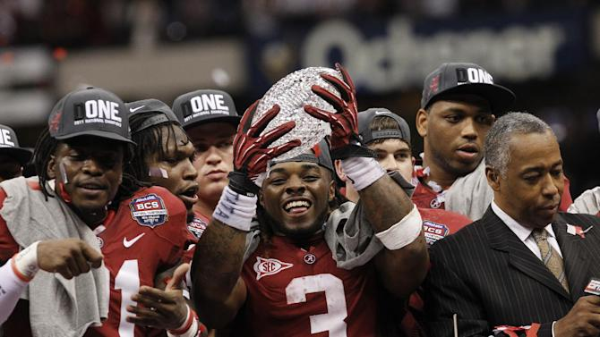 FILE - In this Jan. 9, 2012, file photo, Alabama running back Trent Richardson holds up the championship trophy after winning the BCS National Championship NCAA college football game against LSU, in New Orleans. College football may finally get a playoff system of sorts, if the rumblings out of the Big Ten this week are any indication of the current thought process. The conference that helped spike the idea of teams actually earning their spots in the national title game when it was proposed four years ago, seems to be warming up to it now. (AP Photo/Dave Martin, File)