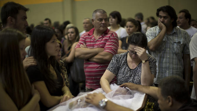 Relatives and friends mourn on the coffin containing the remains of a fire victim at a gymnasium where bodies were brought for identification in Santa Maria city, Rio Grande do Sul state, Brazil, Sunday, Jan. 27, 2013.  A fast-moving fire roared through the crowded, windowless Kiss nightclub in southern Brazil early Sunday, within seconds filling the space with flames and a thick, toxic smoke that killed more than 230 panicked partygoers who gasped for breath and fought in a stampede to escape.(AP Photo/Felipe Dana)