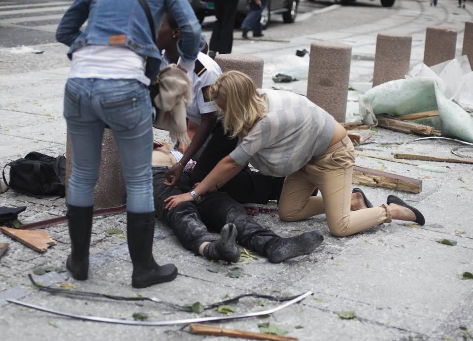 A victim is treated outside government buildings in the center of Oslo, Friday July 22, 2011, following an explosion that tore open several buildings including the prime minister's office, shattering windows and covering the street with documents. (AP Photo/Fartein Rudjord)  NORWAY OUT