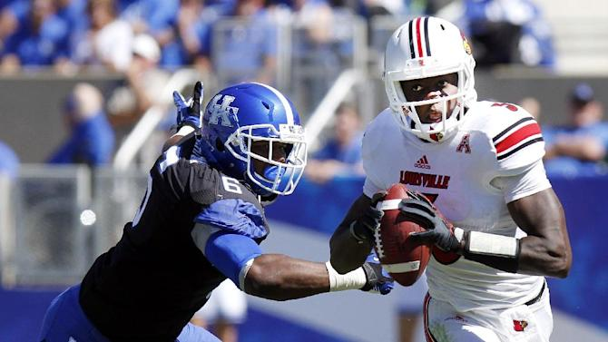 In this Sept. 14, 2013, file photo, Kentucky's Jason Hatcher, left, pursues Louisville's Teddy Bridgewater during an NCAA college football game in Lexington, Ky. Hatcher hasn't taken long fulfilling his wish to become part of Kentucky's defensive rotation and has worked himself into the mix at two positions--end and outside linebacker