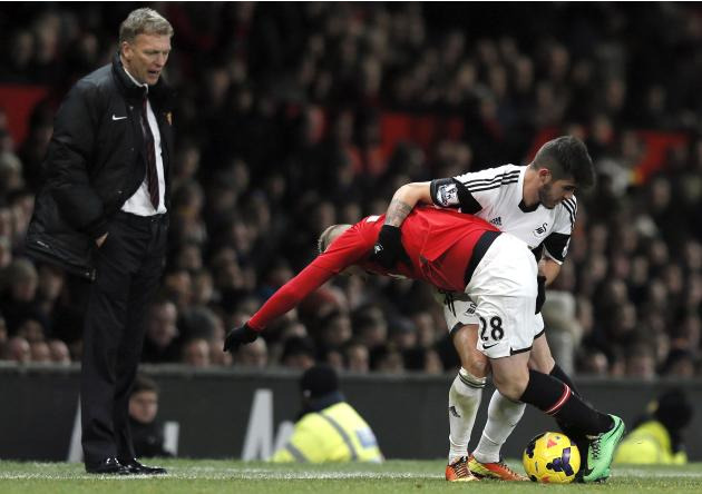 Manchester United's Buttner challenges Swansea City's Pozuelo as his manager Moyes watches during their English Premier League soccer match at Old Trafford in Manchester