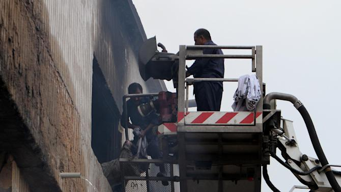 Pakistani rescue workers pull out a dead body from a burnt garment factory in Karachi, Pakistan on Wednesday, Sept. 12, 2012. Pakistani officials say the death toll from devastating factory fires that broke out in two major cities has risen to 128. (AP Photo/Fareed Khan)