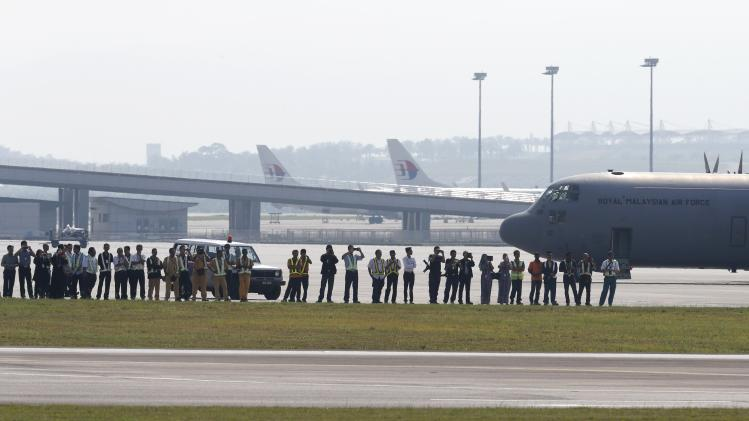 Airport workers and staff watch the repatriation ceremony for the remains of victims of the Malaysia Airlines flight MH17 disaster at the Bunga Raya complex of KLIA airport in Sepang