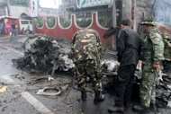 Investigators look for evidence in the wreckage after a car bomb explosion in Cotabato city on the southern Philippines island of Mindanao on August 5, 2013. The powerful bomb which was heard for kilometres around killed six people Monday in a city where the United States and other governments earlier warned of a terror threat
