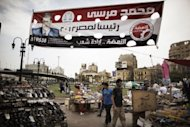 Egyptians walk under a banner of the Muslim Brotherhood's presidential candidate Mohammed Mursi in Cairo. Egypt looks set for a run-off presidential vote between Mursi and Mubarak-era minister Ahmed Shafiq, pitting the Islamists who helped oust a dictator against his last premier