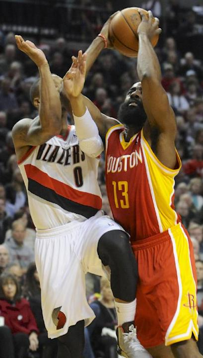Houston Rockets' James Harden (13) shoots against Portland Trail Blazers'  Damian Lillard (0) during the first half of an NBA basketball game in Portland, Ore.,Thursday Dec. 12, 2013