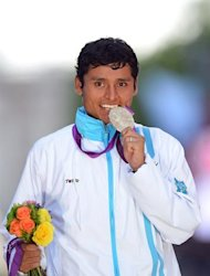 Silver medalist Guatemala's Erick Barrondo bites his medal on the podium after the Men's 20km Race at the London 2012 Olympic Games in London, on August 4, 2012 in London. AFP PHOTO / MIGUEL MEDINA
