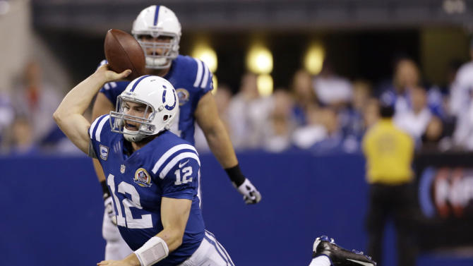 Indianapolis Colts quarterback Andrew Luck (12) throws an interception that was returned by Tennessee Titans' Will Witherspoon 40-yards for a touchdown as he is tackled by Derrick Morgan (91) during the first half of an NFL football game, Sunday, Dec. 9, 2012, in Indianapolis. (AP Photo/Jeff Roberson)