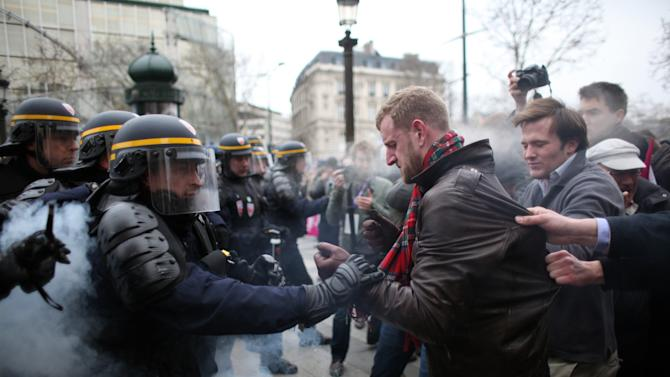 "Protestors clash with riot police officers during an anti gay marriage and gay adoption demonstration, in Paris, Sunday, March. 24, 2013. Thousands of French conservatives, families and activists have converged on the capital to try to stop the country from allowing same-sex couples to marry and adopt children. The lower house of France's parliament approved the ""marriage for everyone"" bill last month with a large majority, and it's facing a vote in the Senate next month. Both houses are dominated by French President Francois Hollande's Socialist Party and its allies. (AP Photo/Thibault Camus)"