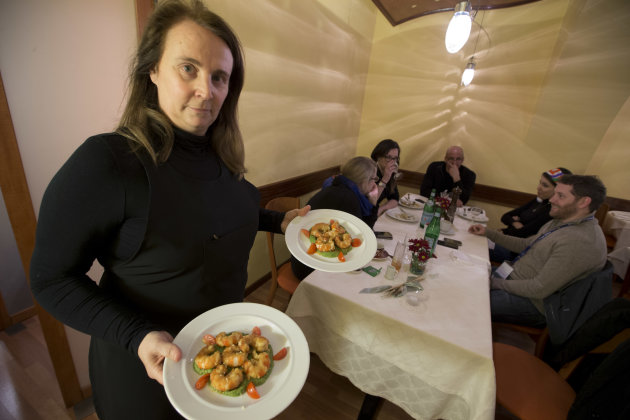 Restaurant owner Patrizia Podetti, center, serves dishes in her Velando restaurant, in Rome, Monday, March 18, 2013. Velando is a favorite dining spot for churchmen, with sleek wooden furnishings, sub