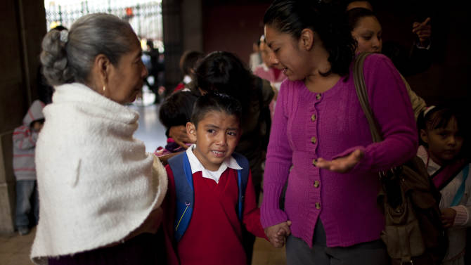 """Diego Angel is consoled by his mother Dulce Castro, right, and grandmother Margarita as he is escorted to the first day of classes in Mexico City, Monday, Aug. 19, 2013. Mexican children returned to classrooms Monday, and they were getting a quick lesson: Not just school kids make mistakes. Their brand new textbooks have the kinds of errors that they are supposed to be learning not to make: words written with a """"c'' instead of an """"s,"""" too many commas, not enough accents and at least one city located in the wrong state. (AP Photo/Ivan Pierre Aguirre)"""