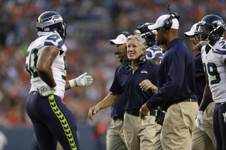 Seattle Seahawks head coach Pete Carroll, center, greets Sehawks' K.J. Wright, left, after Wright made an interception in the first half of an NFL football preseason game against the Denver Broncos, Saturday, Aug. 18, 2012, in Denver. (AP Photo/Joe Mahoney)