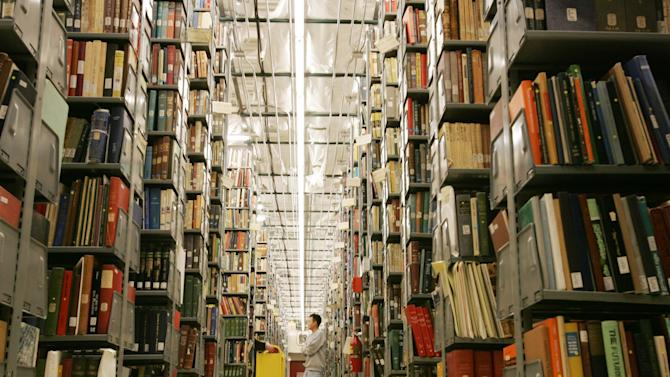 FILE-In this Monday, Dec. 13, 2004, file photo, Vince Lee, 34, a library staffer at the University of Michigan's Buhr Shelving Facility, stands among the 2.4 million books that will be digitized in Ann Arbor, Mich. Google and U.S. publishers settled a longstanding dispute over Google's book-scanning project Thursday, Oct. 4, 2012. Google already has scanned more than 20 million books. Publishers and authors sued, saying the project violated their copyrights. (AP Photo/The Detroit News, Mandi Wright)