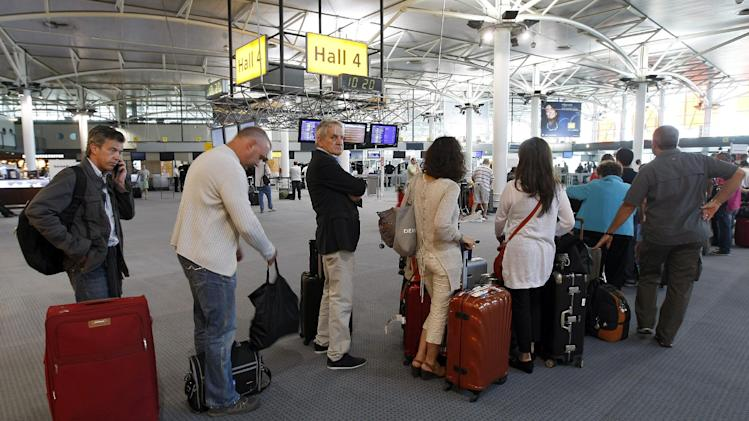 Passengers wait for a flight at Marseille-Provence Airport, in Marignane, southern France, Tuesday, June 11, 2013. France's main airports have cut their flight timetables in half to cope with a three-day strike by air traffic controllers.  The Civil Aviation Authority said that some 1,800 flights were cut Tuesday in France to protest against a plan to centralize control of Europe's air space. (AP Photo/ClaudeParis)