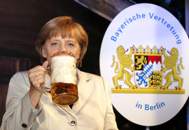 German Chancellor Merkel drinks a mug of beer during the opening of the Oktoberfest in Berlin