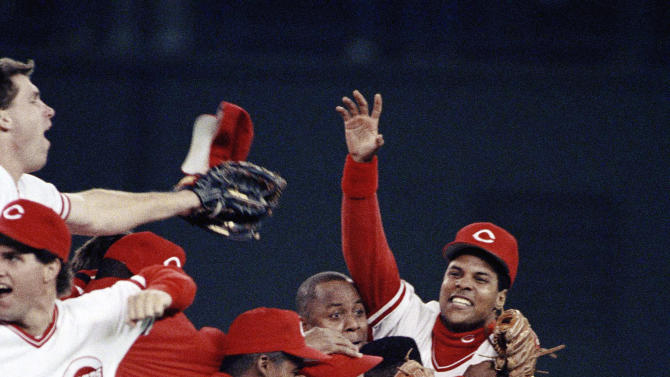 FILE - In this Oct. 12, 1990 file photo, members of the Cincinnati Reds, including Barry Larkin, wearing hat and facing camera at far right, celebrate on the field following their clinching of the NLCS over the Pittsburgh Pirates with a 2-1 win, at Riverfront Stadium in Cincinnati.  Larkin has been elected to baseball's Hall of Fame. The shortstop received 86 percent of the vote in balloting announced Monday, Jan. 9, 2012 by the Baseball Writers' Association of America. (AP Photo/Rusty Kennedy, File)