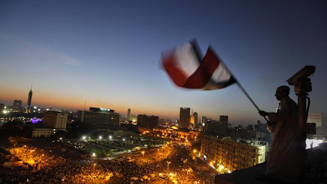 An Egyptian protester waves a national flag over Tahrir Square, the focal point of Egyptian uprising as opponents of President Mohammed Morsi are gathered in Cairo, Egypt, Friday, June 28, 2013. Tens of thousands of backers and opponents of Egypt's Islamist president held competing rallies in the capital Friday and new clashes erupted between the two sides in the country's second largest city, Alexandria, in a prelude to massive nationwide protests planned by the opposition this weekend demanding Mohammed Morsi's removal. (AP Photo/Amr Nabil)