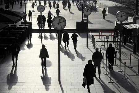 Workers walk past clocks showing a time of 12 minutes past 12 noon, on this century's last sequential date, in a plaza in the Canary Wharf business district of London