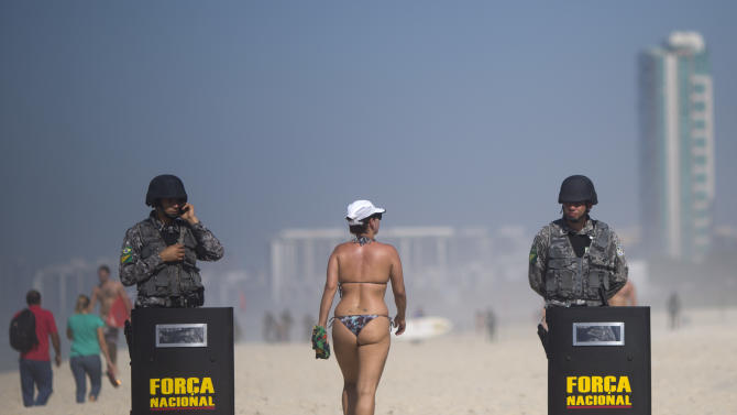 A beach goer walk past National Guard officers at the Barra da Tijuca beach before the auction of the Libra oil field, Brazil's largest single offshore find, in Rio de Janeiro, Brazil, Monday, Oct. 21, 2013. Monday's oil auction is the first in Brazil since the government created new production-sharing agreements. (AP Photo/Felipe Dana)