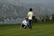 <p>Chinese tourists pose for photos at a golf course which has been closed for over three years at the Mount Kumgang international tourist zone in North Korea on September 1, 2011. Foreigners visiting North Korea can now take their own mobile phones into the country, Chinese state media reported Sunday, citing an employee with the operator of the country's mobile network.</p>