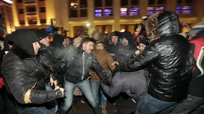 Supporters and opponents of Russian opposition activist and anti-corruption crusader Alexei Navalny clash during unsanctioned protest in Manezhnaya Square in Moscow, Russia, Tuesday, Dec. 30, 2014. The unsanctioned protest came hours after Alexei Navalny was found guilty of fraud and given a suspended sentence. Navalny, who has been under house arrest since February, is accused of breaking the terms of his house arrest to attend the rally and was detained by police as he approached the site of the protest. (AP Photo/Ivan Sekretarev)