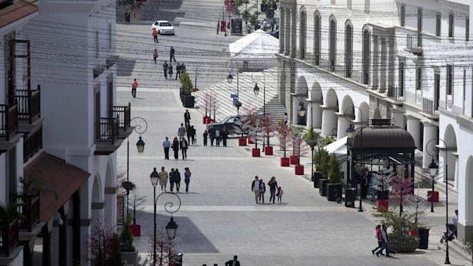 In this Nov. 25, 2012 photo, visitors walk in Paseo Cayala, a nearly independent city on the edges of Guatemala City. Cayala's backers promote the development as a safe haven in a troubled country, one with an unusual degree of autonomy from the chaotic capital. It also embraces a school of urban planning that advocates a return to a traditional concept of a city, with compact, agreeable spaces where homes and shops are intermixed. (AP Photo/Moises Castillo)