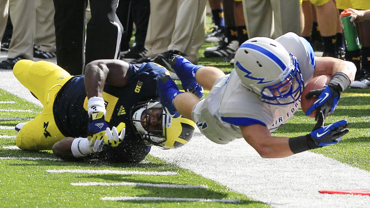 Air Force running back Cody Getz stretches for yardage as he is pushed out of bounds by Michigan cornerback Courtney Avery (5) during the first quarter of an NCAA college football game at Michigan Stadium in Ann Arbor, Mich., Saturday, Sept. 8, 2012. (AP Photo/Carlos Osorio)