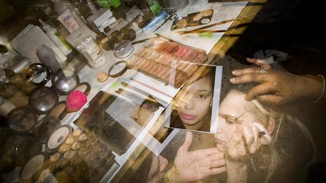 In this photo made with multiple flash exposures, a model is prepared backstage before the Jeremy Scott Fall 2013 fashion show during Fashion Week, Wednesday, Feb. 13, 2013, in New York. (AP Photo/John Minchillo)