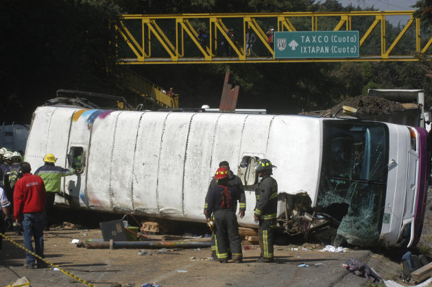Emergency responders stand next to a passenger bus that was struck by a cargo truck in a highway on the outskirts of Mexico City, Thursday April 12, 2012. The bus was carrying students from the Nation