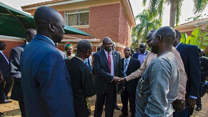South Sudan's rebel leader Riek Machar (C) greets people as he arrives to hold a press conference in Kampala