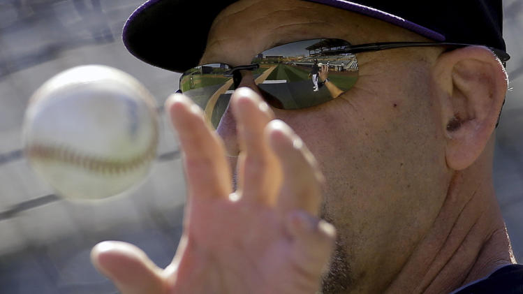 Colorado Rockies manager Walt Weiss hits infield practice before a spring training baseball game against the Oakland Athletics in Scottsdale, Ariz., Saturday, March 8, 2014