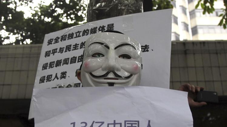 "A supporter of Southern Weekly newspaper wears a Guy Fawkes mask while protesting with a banner that reads ""1.3 billion Chinese have rights to their own voice and do not want to be represented'' outside the newspaper's headquarters in Guangzhou in south China's Guangdong province Tuesday Jan. 8, 2013.  Free-speech protesters in masks squared off against flag-waving communist loyalists in a southern Chinese city Tuesday as a dispute over censorship at a newspaper spilled into the broader population, with authorities shutting microblog accounts of supporters of the paper. (AP Photo) CHINA OUT"