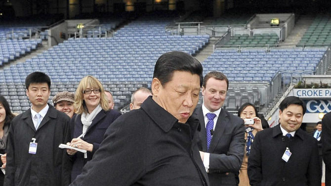 FILE - In this file photo taken Sunday, Feb. 19, 2012, Chinese Vice President Xi Jinping kicks a football during visit to Croke Park Stadium, Dublin, Ireland.  Xi, 59 and the country's vice president is expected to take over as head of the ruling party in November, 2012, before becoming president in 2013 of an increasingly assertive China. Tall and heavyset, married to a popular folk singer in the military, Xi is at ease in groups, in contrast to China's typically stiff and aloof leaders, such as current President Hu Jintao. (AP Photo/Brendan Moran/Pool, File)