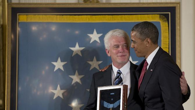 President Barack Obama stands with Ray Kapaun, nephew of Chaplain (Captain) Emil J. Kapaun, U.S. Army, as he awards the Medal of Honor posthumously to Chaplain Kapaun in the East Room of the White House in Washington, Thursday, April 11, 2013. Chaplain Kapaun will receive the Medal of Honor posthumously for his extraordinary heroism while serving with the 3d Battalion, 8th Cavalry Regiment, 1st Cavalry Division during combat operations against an armed enemy at Unsan, Korea and as a prisoner of war from November 1-2, 1950.(AP Photo/Carolyn Kaster)