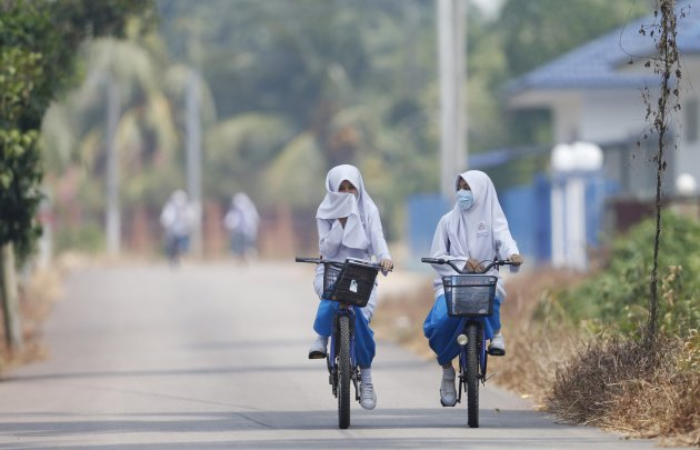 Students, one wearing a face mask and the other covering her mouth with her headscarf, leave for home after an early dismissal from school due to the haze in Muar
