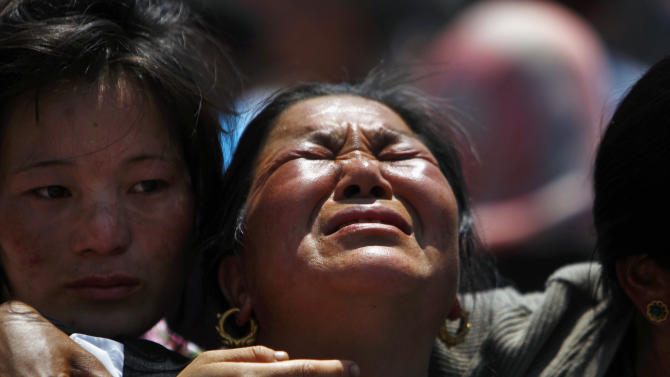 Relatives of mountaineers, killed in an avalanche on Mount Everest, cry during the funeral ceremony in Katmandu, Nepal, Monday, April 21, 2014. Buddhist monks cremated the remains of Sherpa guides who were buried in the deadliest avalanche ever recorded on Mount Everest, a disaster that has prompted calls for a climbing boycott by Nepal's ethnic Sherpa community. The avalanche killed at least 13 Sherpas. Three other Sherpas remain missing and are presumed dead. (AP Photo/Niranjan Shrestha)