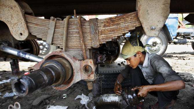 A young boy cleans parts of a truck on World Day Against Child Labor in New Delhi, India, Tuesday, June 12, 2012. This day serves as a catalyst for the growing worldwide movement against child labor. (AP Photo/Saurabh Das)