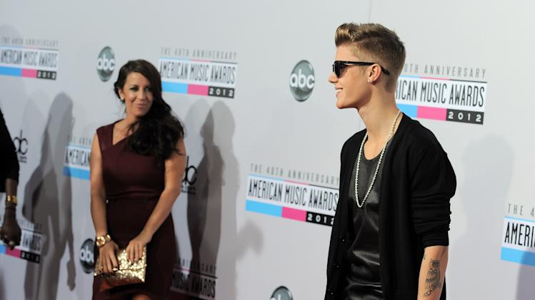 Justin Bieber, right, and Pattie Mallette arrive at the 40th Anniversary American Music Awards on Sunday, Nov. 18, 2012, in Los Angeles. (Photo by Jordan Strauss/Invision/AP)