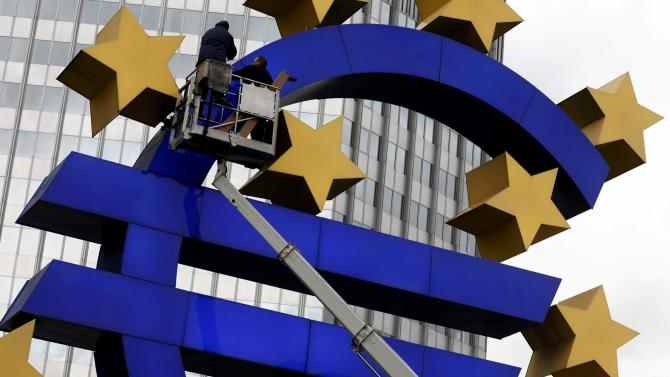 Combination picture shows workers maintaining and later dismanteling Euro sculpture in front former ECB headquarters in Frankfurt