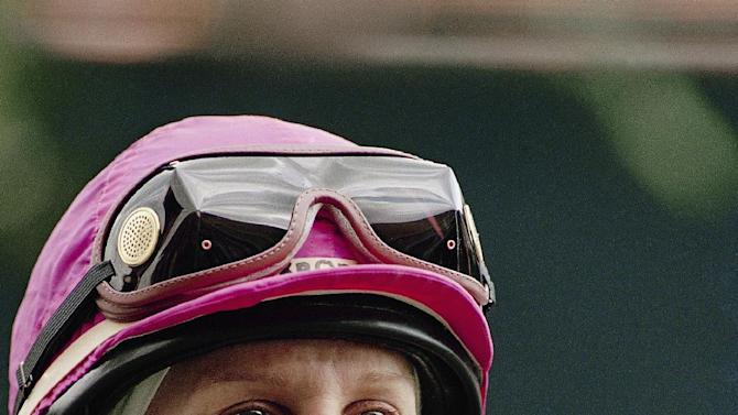 FILE - In an April 17, 1993 file photo jockey Julie Krone smiles prior to the start of the 1993 Wood Memorial at Aqueduct in New York.  Krone is among this years inductees to the National Women's Hall of Fame. (AP Photo/Mark Lennihan, file)